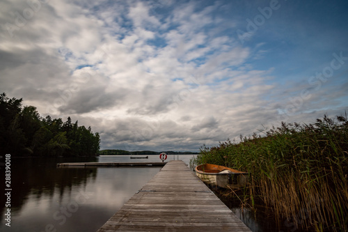 Fotobehang Bleke violet lake in Sweden with a landing stage in the foreground