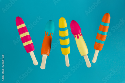 Multi-colored vibrators in the form of ice cream on a stick on a blue background hang in the air Fototapete
