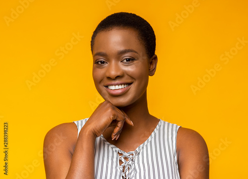 Interested smiling african american girl touching her chin Wallpaper Mural
