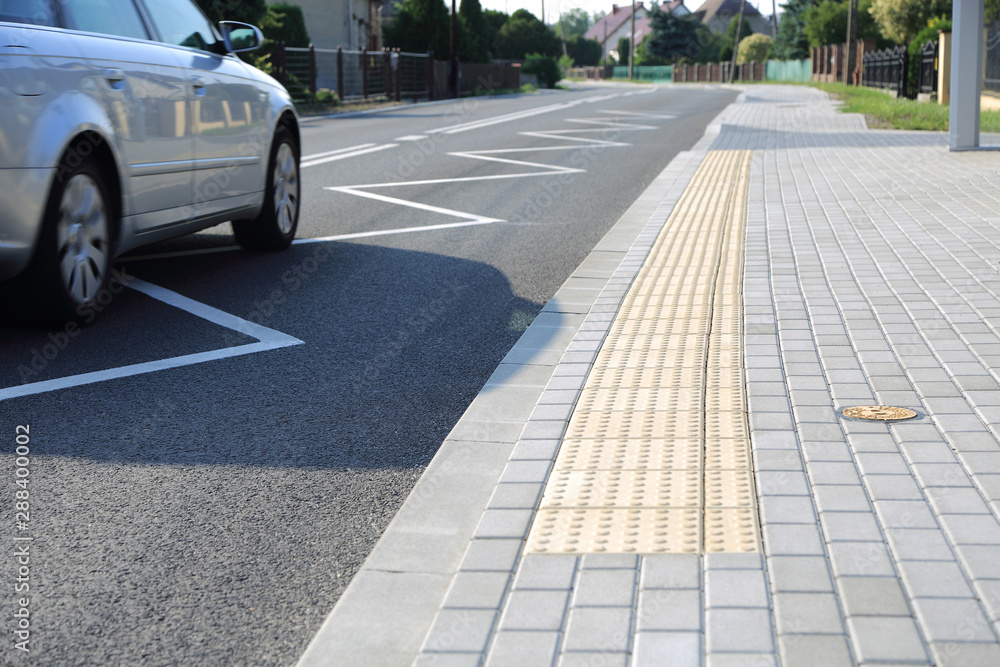 Fototapeta Droga asfaltowa, chodnik i samochó osobowy w obszarze zabudowanym.