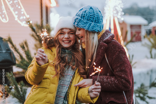 Canvastavla  Joyful best friends having fun on Christmas market