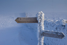 At The Summit Of Penyghent Part Of The Yorkshire Three Peaks, A Pennine Way Sign Covered In Snow