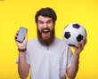 canvas print picture - Photo of excited supporter, holding mobile and soccer ball over yelow background