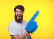 canvas print picture - Photo of handsome bearded guy, with big fan glove, pointing away over eyellow background