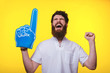 canvas print picture - Photo of screaming supporter, with big blue finger glove, over yellow background