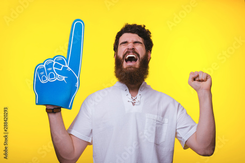 Photo Photo of screaming supporter, with big blue finger glove, over yellow background