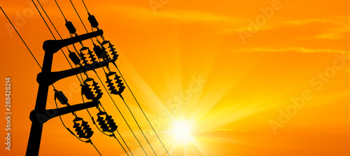 close up electricity power line tower over orange color sunset sky with shining sun