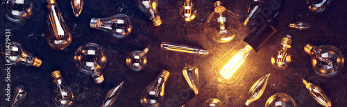 Obraz Vintage old light bulb glowing yellow on rough dark background surrounded by burnt out bulbs. Idea, creativity concept. - fototapety do salonu