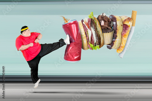 Overweight man kicking soft drink and fast food Wallpaper Mural
