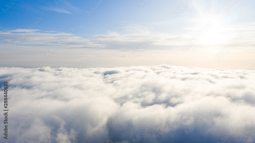 Fototapety, obrazy: Aerial view White clouds in blue sky. Top view. View from drone. Aerial bird's eye view. Aerial top view cloudscape. Texture of clouds. View from above. Sunrise or sunset over clouds
