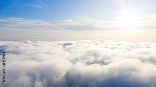 Aerial view White clouds in blue sky. Top view. View from drone. Aerial bird's eye view. Aerial top view cloudscape. Texture of clouds. View from above. Sunrise or sunset over clouds - 288440635