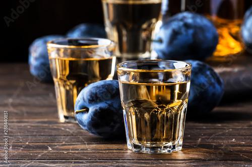 Fotografia Slivovica - plum brandy or plum vodka, hard liquor, strong drink in glasses on o