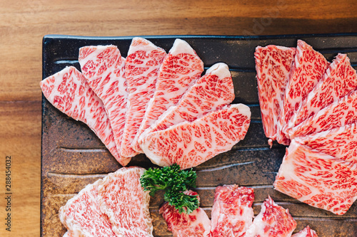 Close-up top view of Premium Rare Slices many parts of Wagyu A5 beef with high-marbled texture on stone plate served for Yakiniku (Grilled Meat).