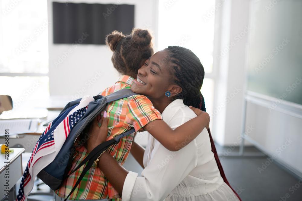 Fototapety, obrazy: Girl hugging her pleasant teacher while feeling thankful