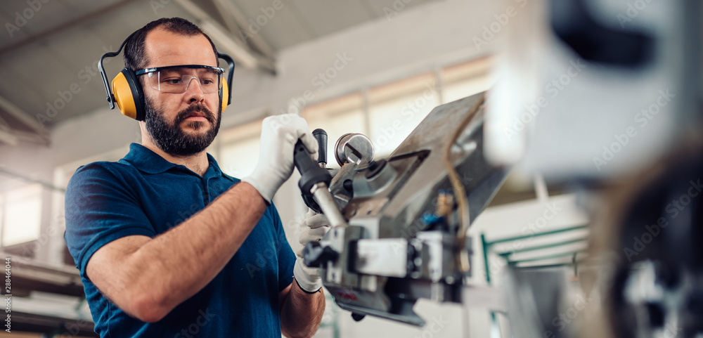 Fototapety, obrazy: Factory worker operating band saw cutting machine