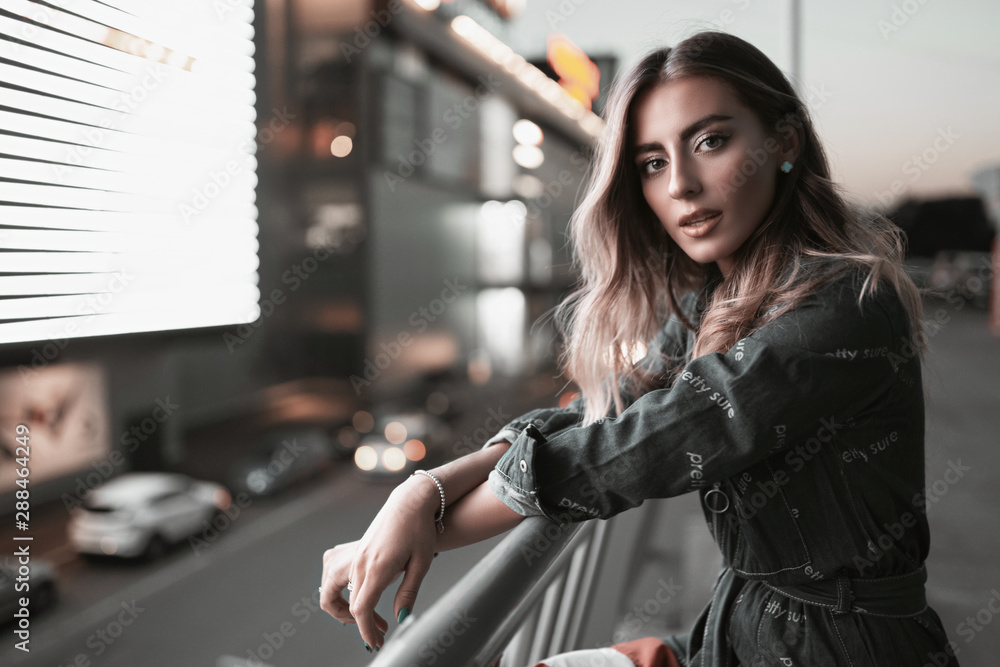 Fototapety, obrazy: Street portrait of stylish fashion girl in denim overalls on parking at night. Young woman posing in evening in neon light near shops with beautiful hair style