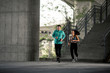 Handsome young couple running in urban environment at sunny day