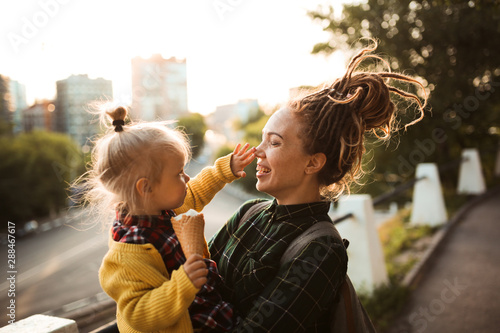 Photo  mom with dreadlocks and toddler eating ice cream