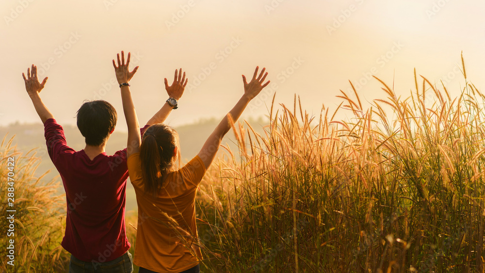 Fototapety, obrazy: Asian woman and man standing and hand up in meadow and looking far away at sunrise time, Selective focus.;