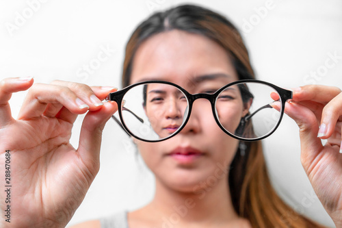 Fotografía Asian woman holding glasses on white background, Selective focus on glasses , myopia and eyesight problem concept