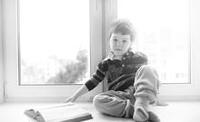 The Little Boy Is Reading A Bo...