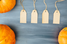 Thanksgiving Background. Pumpkin With Four Tags On Gray Wood Table Background With Copy Space. Thanksgiving And Halloween Concept. View From Above. Top View. Copy Space For Text And Design