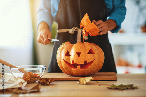 Photo Stands Coffee bar hands of man cutting pumpkin to halloween.