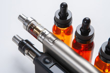 Silver And Black Vapes Next To The Vials. Liquids For Electronic Cigarettes. Smoking E-cigarettes. Vaping Accessories. Devices For Smoking Electronic Cigarettes.