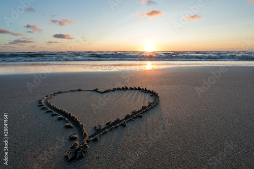 heart in the sand at sunset