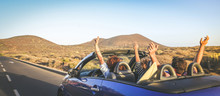 Back View Group Three Euphoric Friends In Convertible Car Twisting And Waving Two Curly Girls And Charming Bearded Man On Vacation Having Fun In Topless Auto Arms Up Palms Open Driving In The Sunlight