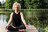 Medytująca, zrelaksowana, piękna kobieta. Joga na drewnianym pomoście. Pozycja lotosu z widokiem na jezioro.