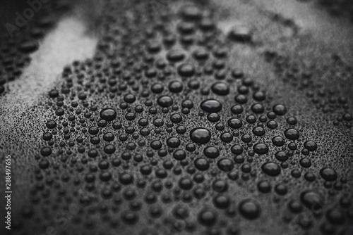 Closeup black car paint surface with hydrophobic ceramic coating
