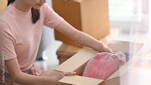Cuadros en Lienzo Cropped shot online small business owner packing drop product on box