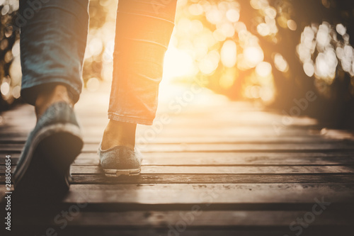 Obraz Close up woman walk in to the wild with sunset and sunlight background. - fototapety do salonu