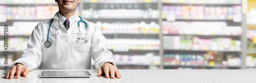 Photo sur Toile Pharmacie Male pharmacist sitting at table with tablet computer in pharmacy office. Medical healthcare staff and drugstore business.