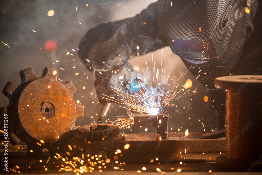 Fototapety, obrazy: Welder is welding metal part in industrial workshop.