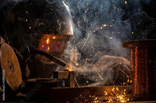 Türaufkleber Logo Welder is welding metal part in industrial workshop.