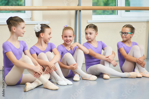 Five young ballerinas sitting on the floor. Cute little ballet dancers in purple leotards having a rest. Beautiful and talented girls. Stock Photo | Adobe Stock