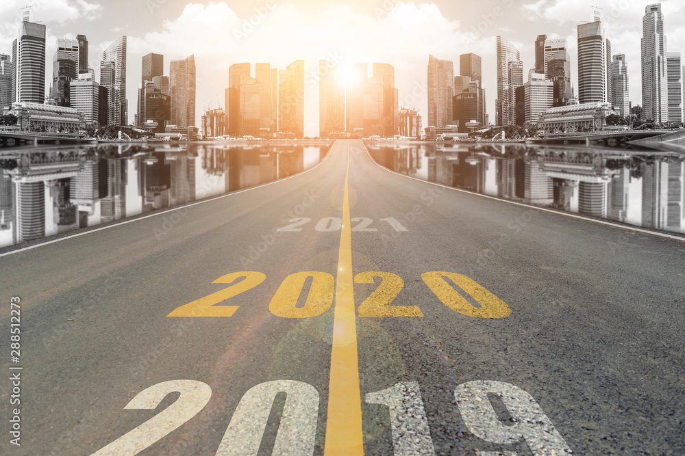 Fototapeta The number 2020 symbol represents the new year on the road heading to the city with beautiful skyscrapers background, New Year's and business target concepts.