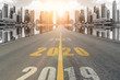 canvas print picture - The number 2020 symbol represents the new year on the road heading to the city with beautiful skyscrapers background, New Year's and business target concepts.