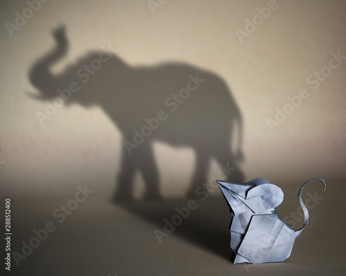 Obraz Concept of hidden potential. A paper figure of a mouse  that fills the shadow of  an elephant. 3D illustration - fototapety do salonu