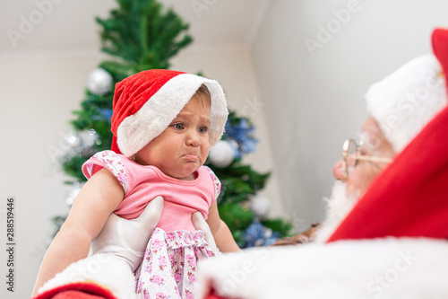 Foto Little baby scared of Santa Claus