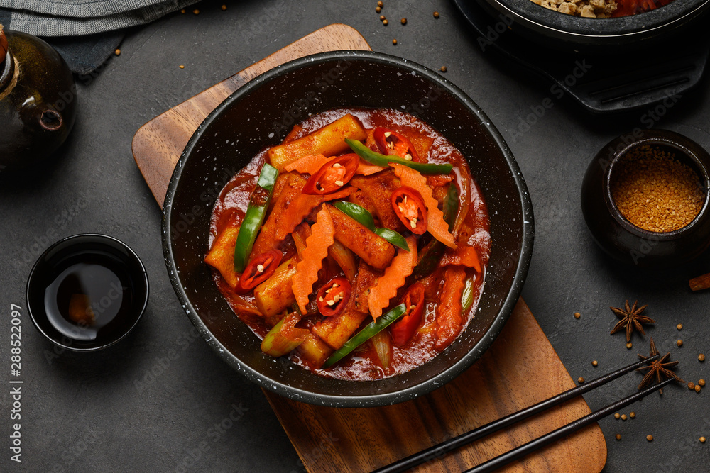 Fototapeta Korean Food Style : Top view of Hot and spicy Stir-fried rice cake ( Tteokbokki ) put in the black bowl or dish and placed on a wooden tray