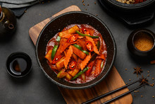 Korean Food Style : Top View Of Hot And Spicy Stir-fried Rice Cake ( Tteokbokki ) Put In The Black Bowl Or Dish And Placed On A Wooden Tray