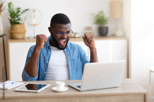 Young african businessman sitting at his desk, celebrating success with arms raised while looking at his laptop screen