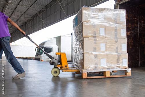 Obraz warehouse logistics and transportation, worker with hand pallet truck unloading cargo pallet shipment at dock warehouse. - fototapety do salonu