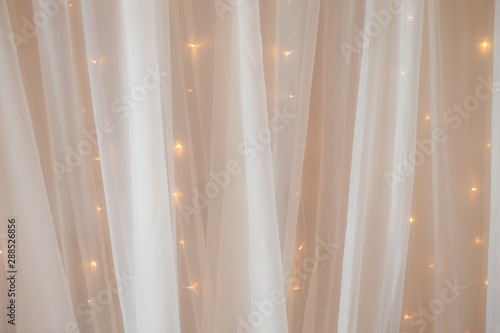Fototapeta Transparent tulle with lights at the wedding ceremony, a place for photographing