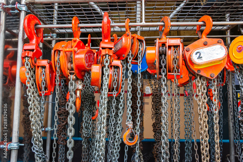 Fototapety, obrazy: Multiple chain hoists hanging in a rack ready for use in a industrial environment, picture taken in the Netherlands