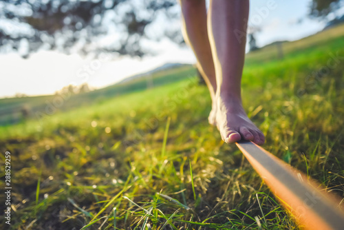 Papel de parede Close up on feet walking on tightrope or slackline outdoor in a city park in sun
