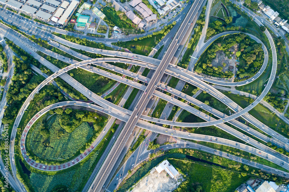 Fototapeta Aerial view of road interchange or highway intersection with busy urban traffic speeding on the road. Junction network of transportation taken by drone.